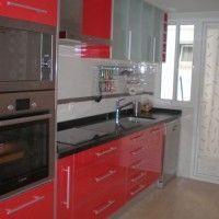 Cocina tipo pasillo con muebles rojos
