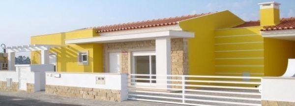 Casa amarilla conbinada con revestimiento en piedras for Pintura para exteriores de casa 2016