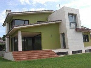 frente casa verde con revestimiento simil piedra blanca