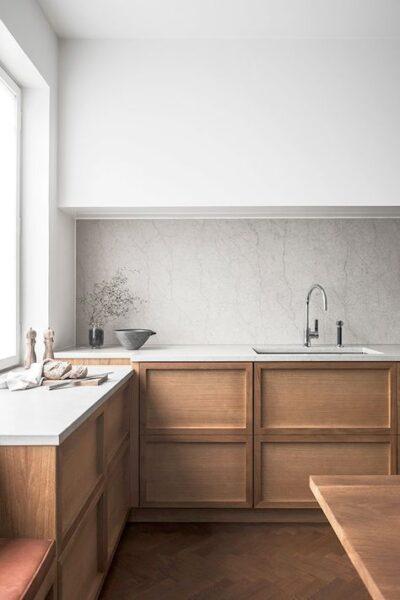 Cocina con muebles de madera y mesada blanca moderna