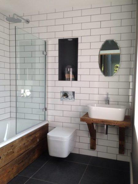 baño con ceramicas blancas y piso negro