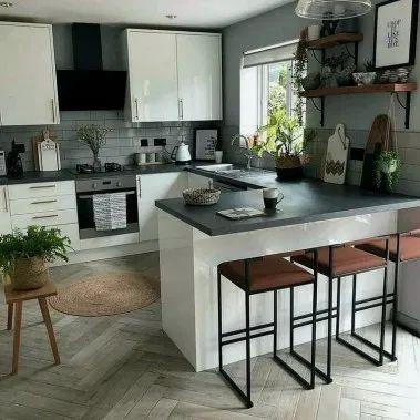 cocina con muebles blancos y mesada negra