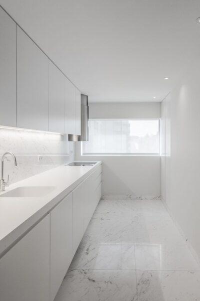 pequeña cocina blanca con piso de marmol